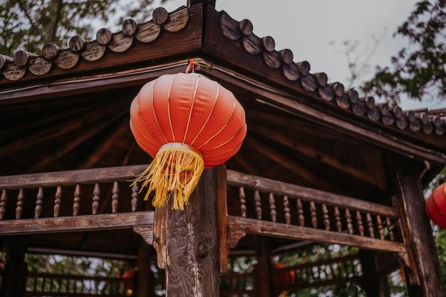 China reist chinese rode lantaarns die op een houten pagode of een gazebo in aardpark hangen voor de chinese banner van de nieuwjaar maanviering Premium Foto