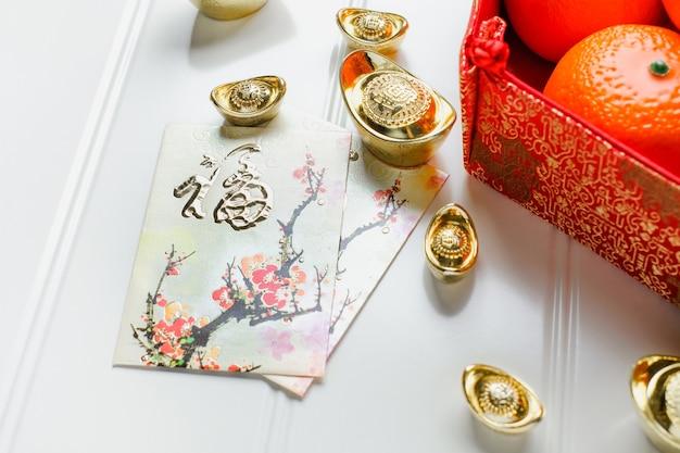Chinees nieuw jaar, rood enveloppakket (ang pow) met gouden blokken en sinaasappelen en bloem Premium Foto
