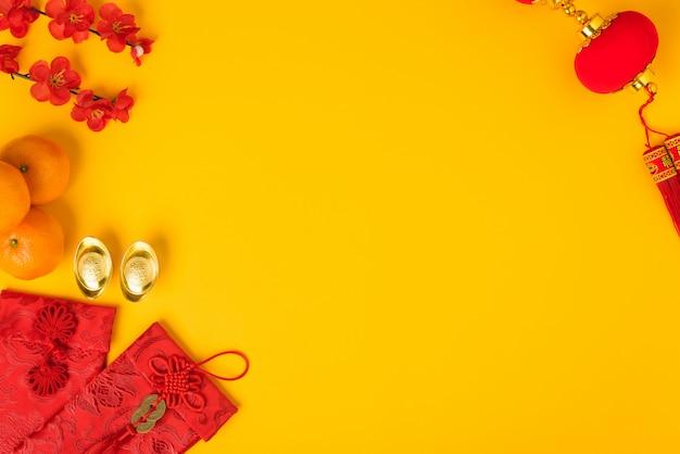 Chinees nieuwjaarfestival, plat lag bovenaanzicht, gelukkig chinees nieuwjaar met rode envelop en goudstaaf op geel en copyspace Premium Foto
