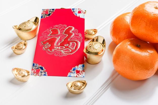 Chinees nieuwjaars rood ang pow met gouden baren en mandarijn op lijst, chinees taalgemiddelde Premium Foto
