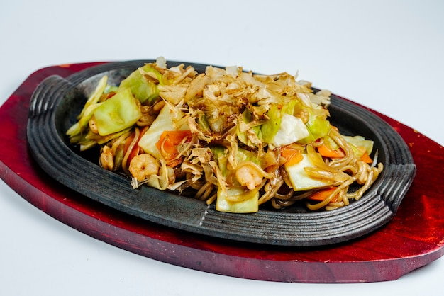 Chinese garnalen roerbak noedels met kool en wortel in gietijzeren pan Gratis Foto