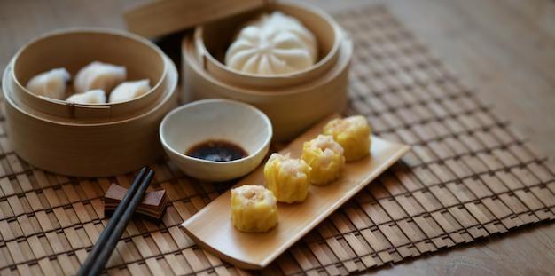 Chinese gestoomde bol en gestoomd varkensvleesbroodje in een bamboestoomboot met eetstokje op houten lijst Premium Foto