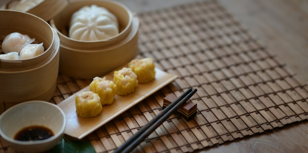 Chinese gestoomde bol en gestoomd varkensvleesbroodje in een bamboestoomboot met eetstokje Premium Foto