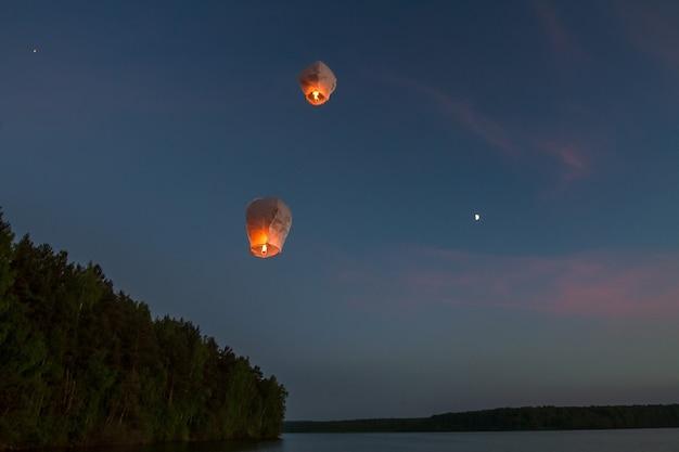 Chinese vliegende lantaarns, vliegen over meer in het donker Premium Foto