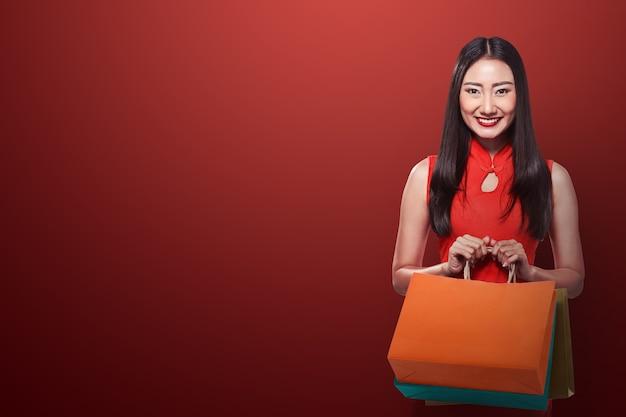 Chinese vrouw in cheongsam jurk met boodschappentas Premium Foto