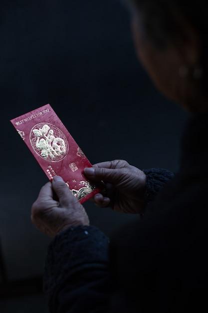 Chinese vrouw met een traditionele rode envelop met chinese nieuwjaarswensen Gratis Foto
