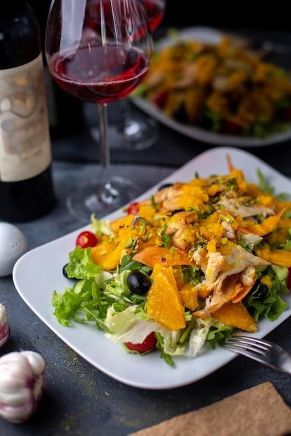 Chips oranje salade met gesneden groenten samen met rode wijn op grijze bureau Gratis Foto