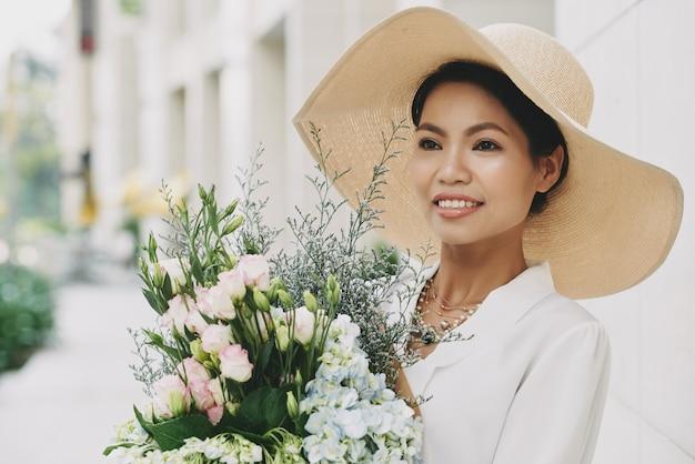 Chique rijke aziatische vrouw in grote strohoed poseren in straat met vers bloemboeket Gratis Foto