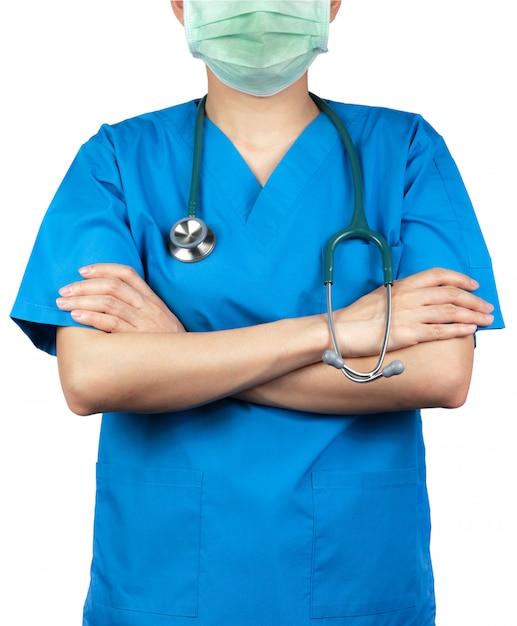 Chirurg arts draagt blauwe scrubs shirt uniform en groen gezichtsmasker. artsentribune met gekruiste wapens en de stethoscoop van de handholding. beroepsbeoefenaar in de gezondheidszorg. Premium Foto