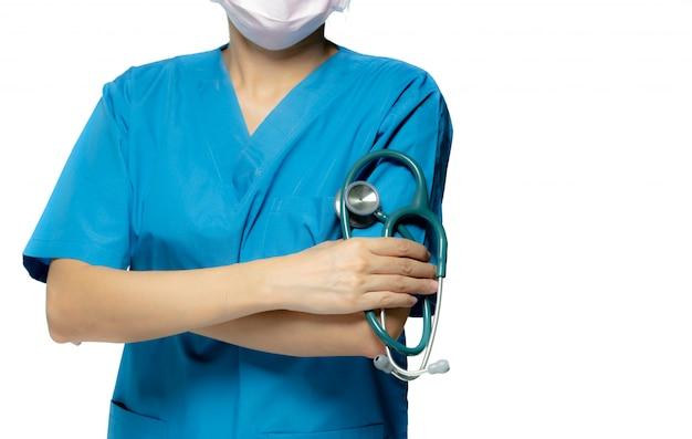 Chirurg arts of verpleegkundige dragen blauwe scrubs uniform en roze gezichtsmasker. artsentribune met gekruiste wapens en de stethoscoop van de handholding. beroepsbeoefenaar in de gezondheidszorg. Premium Foto