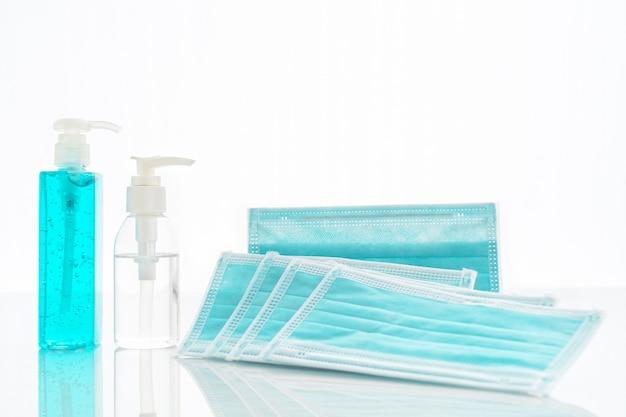 Chirurgisch masker, medische gezichtsmaskers en handdesinfecterende fles met alcoholgel voor bescherming tegen bacteriën en virussen aan dek Premium Foto