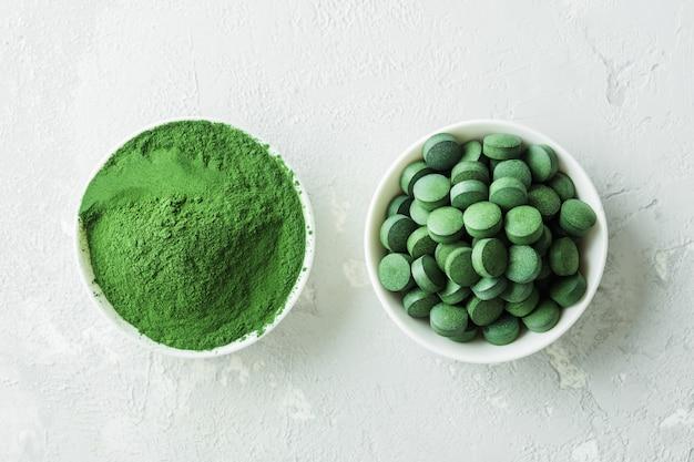Chlorella of spirulina in de vorm van tabletten en poeder op een grijze betonnen achtergrond. Premium Foto