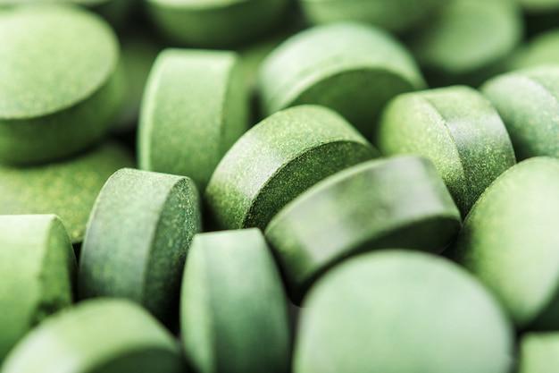 Chlorella of spirulinatabletten sluiten omhoog. bovenaanzicht. textuur van tabletten spirulina of chlorella. Premium Foto
