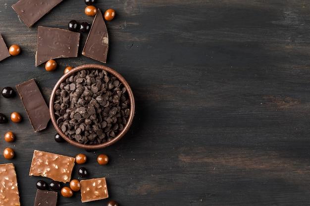 Choco druppels met chocoballs en choco bars in een klei kom op houten tafel Gratis Foto