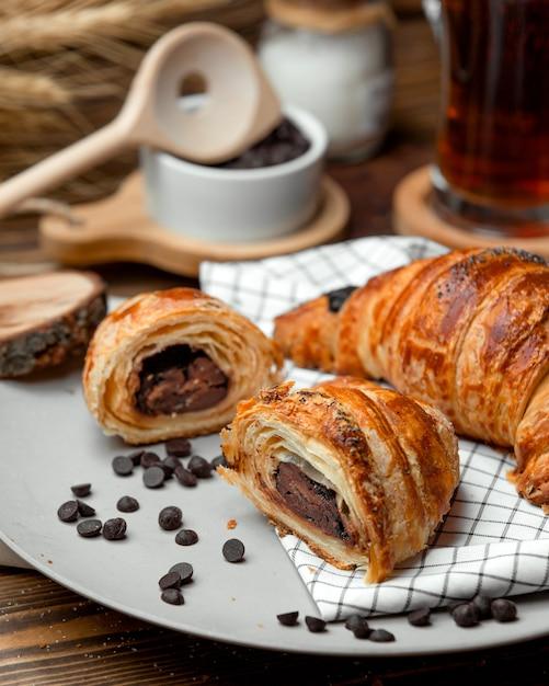 Chocolade bladerdeeg croissant bestrooid met chocoladeschilfers Gratis Foto
