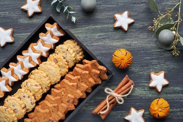 Chocolade chocoladekoekjes, plat met specerijen en winterdecoraties op donker Premium Foto