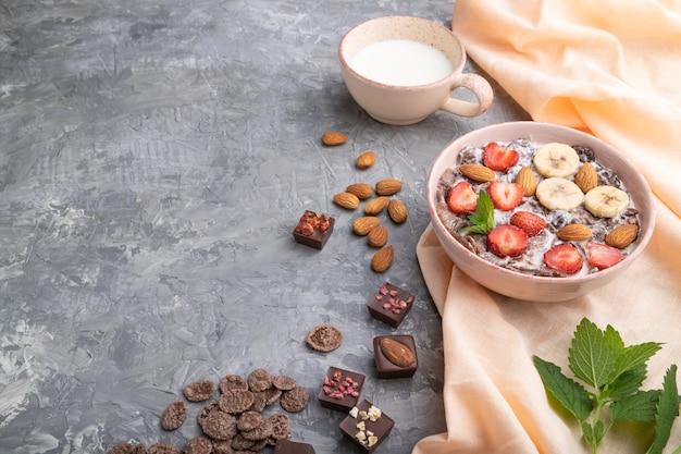 Chocolade cornflakes met melk, aardbei en amandelen in keramische kom Premium Foto