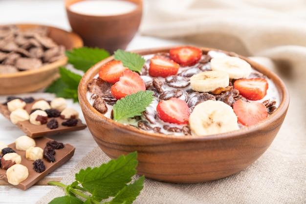 Chocolade cornflakes met melk en aardbei in houten kom Premium Foto