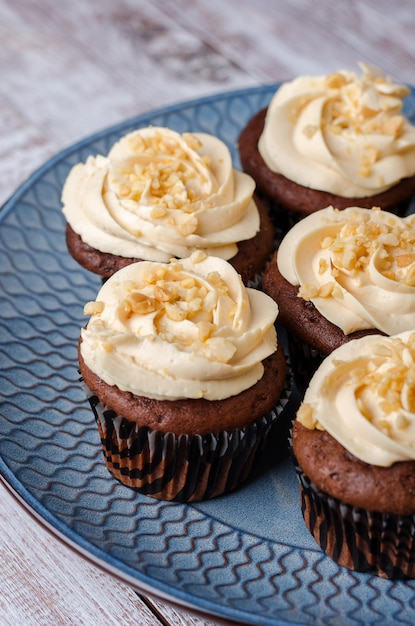 Chocolade cupcakes met karamelcrème versierd met gemalen pinda's op blauwe achtergrond. Premium Foto