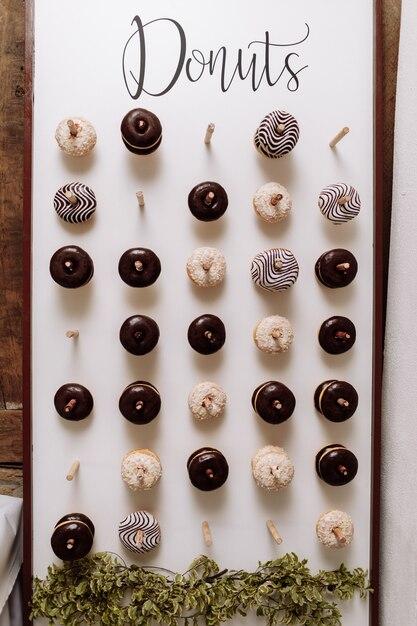 Chocolade donuts voor gasten. feestelijk concept. snoepjes op een trouwdag. bruiloft donuts Premium Foto