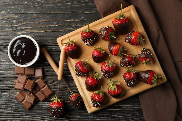 Chocolade fondue. aardbei in chocolade op houten achtergrond, bovenaanzicht Premium Foto