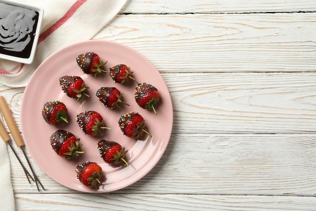 Chocolade fondue. aardbei in chocolade op witte houten achtergrond Premium Foto