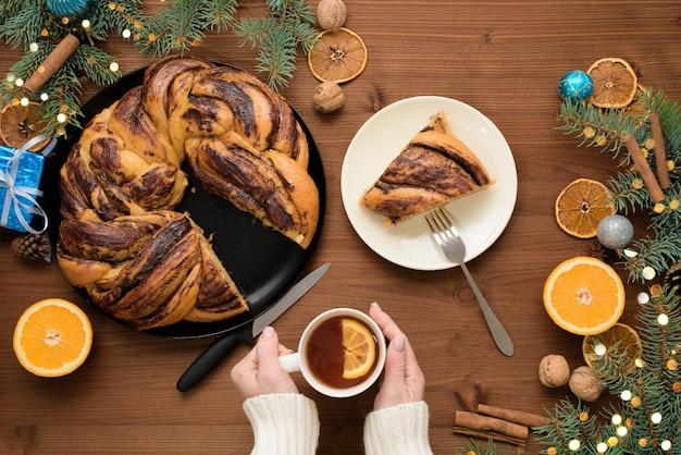 Chocolade kerst grootmoeder in de vorm van een krans met sinaasappelsiroop op een bord in stukjes gesneden. kerstversiering op een houten tafel. Premium Foto