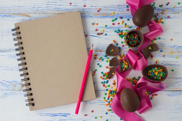 Chocolade-paaseieren, roze lint, kladblok en kleurpotloden, veelkleurige snoepjes van pasen op het oude witte houten oppervlak Premium Foto
