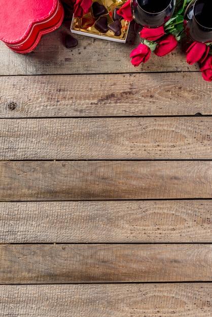 Chocolade, rozen, wijnglazen en hartdoos op houten lijst Premium Foto