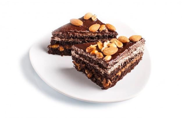 Chocoladecake met karamel, pinda's en amandelen op een witte achtergrond worden geïsoleerd die. Premium Foto