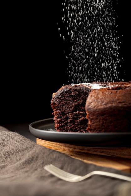 Chocoladecake met suikerpoeder wordt bestrooid op een zwarte plaat die Gratis Foto