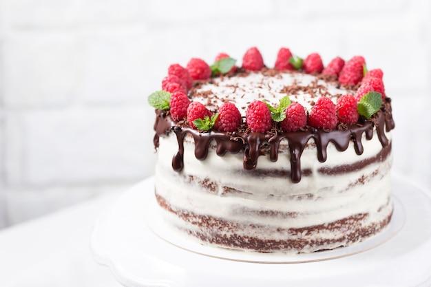 Chocoladecake met witte kaasroom verfraaide ganache en frambozen op een witte caketribune, exemplaarruimte Premium Foto
