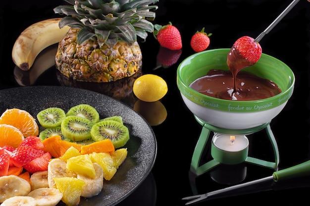 Chocoladefondue met fruitassortiment op zwarte spiegelachtergrond. Premium Foto