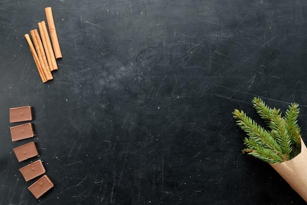 Chocoladekaneel en spar vlakke menings zwarte achtergrondexemplaarruimte Premium Foto