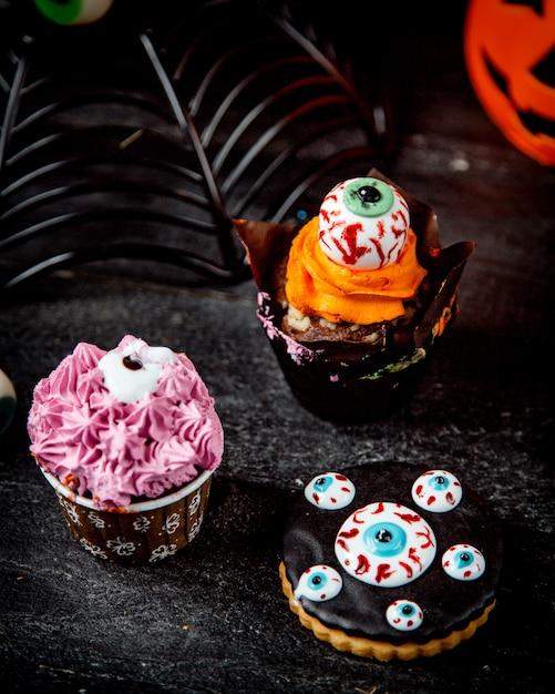 Chocolademuffin met sinaasappelroom en halloween-koekjes Gratis Foto