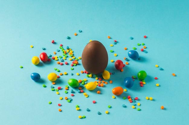 Chocoladepaasei en multi-coloured snoepjes op een blauwe achtergrond. paasviering concept. Premium Foto