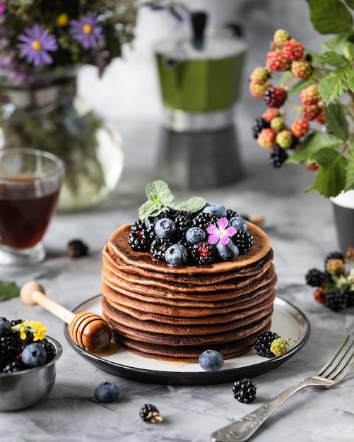 Chocoladepannekoek met bessen en fruit met honing, met vliegende poedersuiker en een boeket wilde bloemen op de tafel. donker Premium Foto