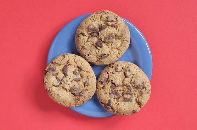 Chocoladeschilferkoekjes op een blauw bord op een rode achtergrond Premium Foto
