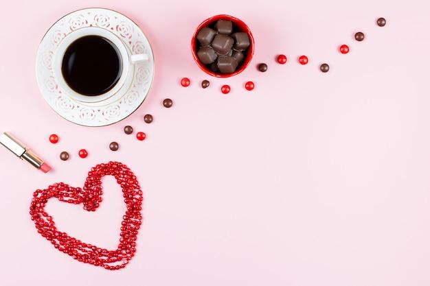 Chocoladesnoepjes, warme drank, lippenstift. vrouwelijke achtergrond in roze, rode en witte kleuren. plat leggen, kopie ruimte. Premium Foto