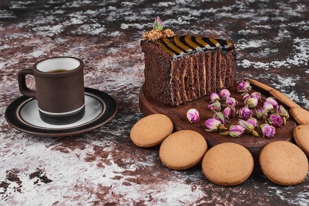 Chocoladetaart en koekjes op een houten bord. Gratis Foto