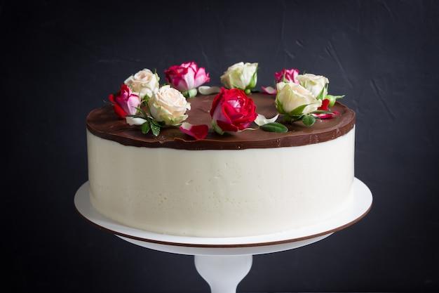 Chocoladetaart met rozen op vintage stand. mooie cake met rode en witte roze bloemen, zwarte achtergrond Premium Foto