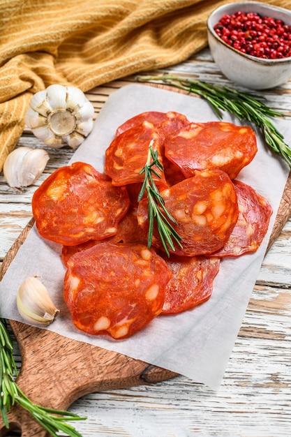 Chorizo worst dun gesneden op een snijplank. spaanse salami met kruiden, paprika, peper. pittig eten. witte achtergrond. bovenaanzicht. Premium Foto