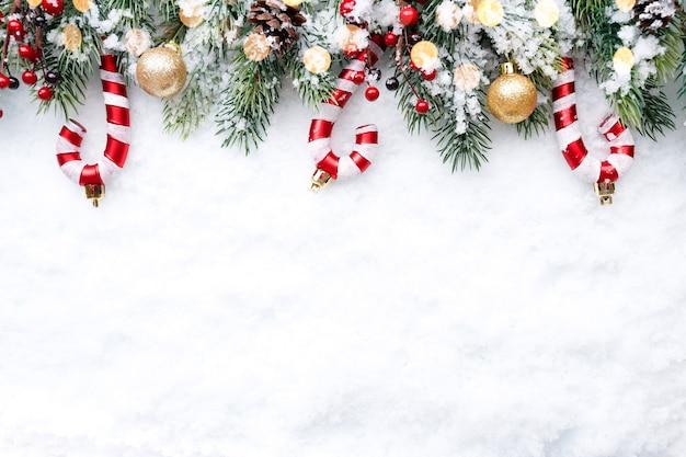 Christmas border - takken met gouden kerstballen, snoepjes en kegels op sneeuw Premium Foto