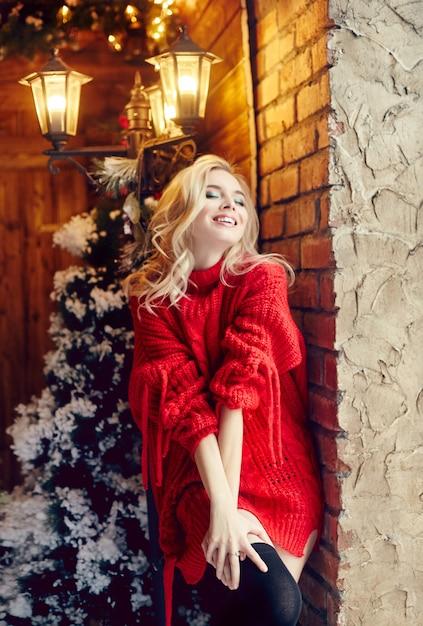 Christmas fashion sexy vrouw blonde in de rode trui, plezier maken en poseren tegen de kerstboom en lantaarnpaal. winter en kerstboom in dorpshuis. meisje met perfecte figuur en glimlach Premium Foto