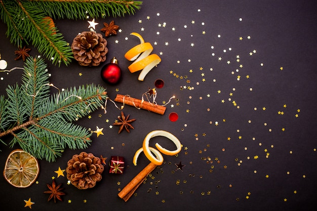 Christmas wenskaart met ambachtelijke geschenkdoos met rood lint. zwarte achtergrond met gouden confetti. Premium Foto