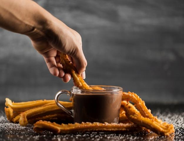 Churros dompelen in een beker gevuld met gesmolten chocolade Gratis Foto