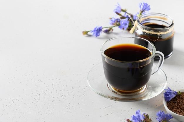 Cichorei wortel koffie in glazen beker en verse bloemen. gezondheidsvoordelen. kopieer ruimte. detailopname. Premium Foto
