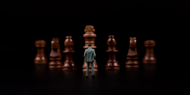 Cijferszakenman die zich voor houten schaak op zwarte geïsoleerde achtergrond bevinden. Premium Foto