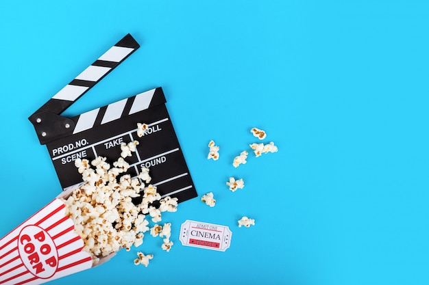 Cinema achtergrond. popcorn en clapperboard op blauw Premium Foto