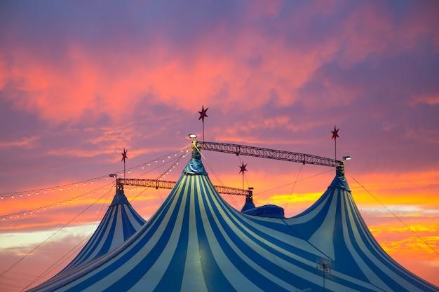 Circustent in een dramatische kleurrijke zonsonderganghemel Premium Foto